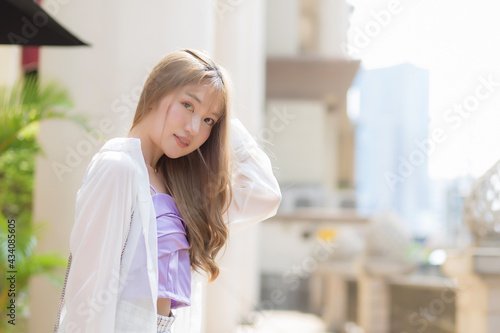 Obraz na płótnie Asian beautiful girl with bronze long hair in purple camisole and white sleeve stands on the street as background on a sunny morning