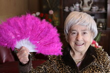 Senior Woman Holding Plumy Pink Feather Hand Fan