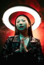 Cyberpunk People. Spiritual Portrait. Future Faith. Blue Neon Light Art Portrait Of Asian Prayer Girl In Black Leather Jacket Namaste With White Halo In Red Color Smoke On Dark.