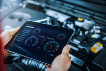 Car Engine Diagnostics. Service Mechanic Using Digital Tablet To Inspect Vehicle Condition