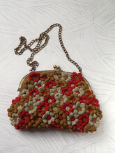 Handmade Crochet Purse Isolated On Blue Rustic Wooden Surface. The Purse Is Made Of Crochet Flowers Joined One To Another By Hand Sewing. Concept Of Art, Design, And Creativity.