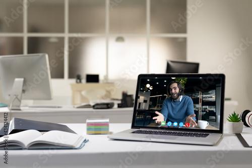 Caucasian man having business video call on screen of laptop on desk