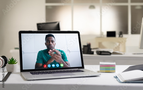 African american man having business video call on screen of laptop on desk