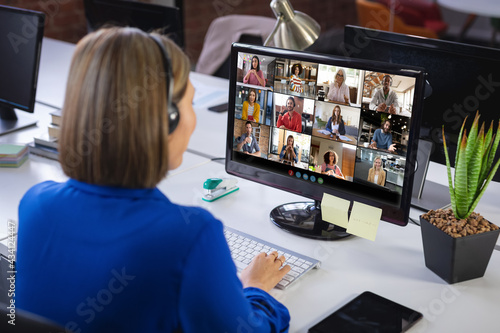 Caucasian businesswoman sitting at desk using computer having video call with colleagues