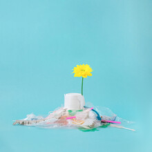Environment Concept Art With Yellow Flower Growing Behind Heap Of Plastic Trash.