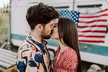 Pareja De Chico Y Chica Juntos Besandose Con La Bandera De Estados Unidos De Fondo En Una Caravana