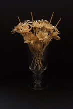 A Glass Vase With A Bouquet Of Flowers Made From Straw