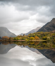 Abandoned Old Welsh Castle Standing Forest Trees Reflecting On Perfect Still Lake Of Water. Mirror Image Reflection Of Fortress Looming Storm Skies Snowdonia Mountains Atmospheric Clouds Dolbadarn