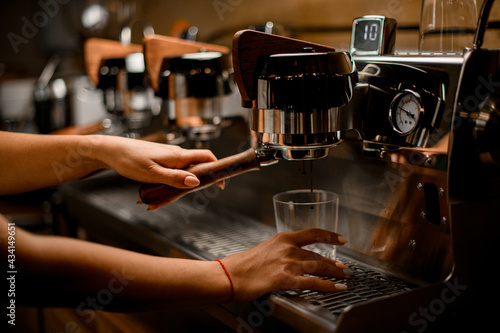Fotografiet view of professional coffee machine with which female barista prepares coffee