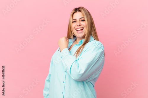 curvy pretty blonde woman feeling happy and facing a challenge or celebrating Fototapet