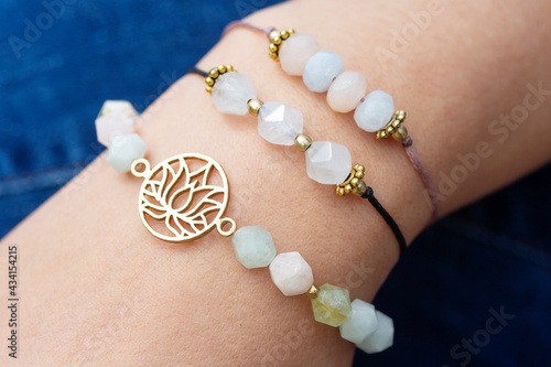 Obraz na plátne Female hand wearing popular gemstone mineral bead yoga bracelets