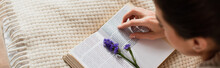 High Angle View Of Blurred Young Woman Reading Book With Purple Flower While Resting On Bed At Home, Banner