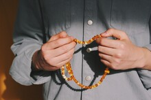 Hands Of Muslim Man Performing Islamic Ritual Chanting / Invocation / Dhikr (with Both Hands) With Orange Rosary & Background