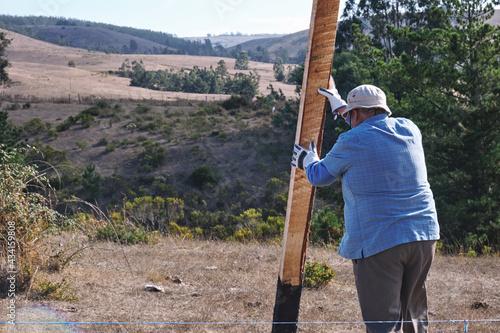 Fotografija Elderly villager man holding a wooden plank