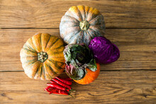 Top View Of Various Pumpkins With Red Cabbage And Red Hot Chili Peppers Arranged On Wooden Table In Kitchen