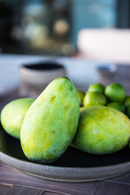 Exotic Green Mangoes On Plate Served On Table With Rip Limes On Sunny Day In Tropical Resort