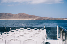 Empty White Chairs On Deck Of Cruise Boat Sailing In Blue Sea Water With Mountain On Shore