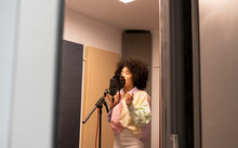 Black Female Singer Performing Song Against Microphone With Pop Filter While Standing And Closed Eyes In Sound Studio