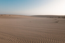 Picturesque View Of Dunes With Uneven Surface And Sandy Hills Under Light Sky In Desert