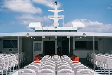 Deck Of Cruise Boat With Empty White Chairs In Row Under Clear Sky With Clouds