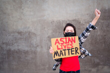 Ethnic Female In Mask And With Carton Placard With Inscription Asian Lives Matter Protesting With Raised Arm In City Street And Looking At Camera