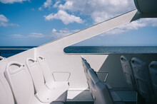 Empty White Chairs On Deck Of Cruise Boat Sailing In Blue Sea Water