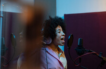 Black Female Singer Performing Song Against Microphone With Pop Filter While Standing And Looking Forward In Sound Studio