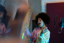 Black Female Singer Performing Song Against Microphone With Pop Filter While Standing With Hand On Hip And Closed Eyes In Sound Studio