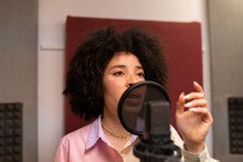 Black Female Singer Performing Song Against Microphone With Pop Filter While Standing With Hand On Hip And Looking Forward In Sound Studio