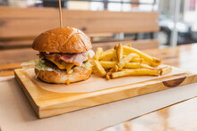 Delicious Fresh Hamburger And Crispy French Fries Served On Wooden Board In Modern Fast Food Restaurant