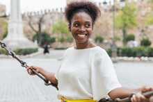 Happy Young African American Female In White Blouse Leaning On Chain Barrier And Looking Away With Toothy Smile While Spending Warm Day On City Square