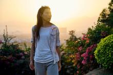 Ethnic Asian Woman Walking In Garden During Sunset Time