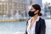 Young Ethnic Female Entrepreneur In Fabric Mask And Formal Clothes Looking Away Against City River In Sunlight