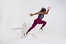 Side View Of Determined African American Sportswoman Jumping With Flying Hair While Looking Forward During Cardio Training