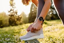 Side View Of Crop Anonymous Sportswoman In Wearable Tracker Tying Shoelaces On Footwear Before Working Out On Meadow In Sunlight