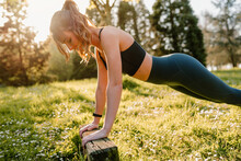 Side View Of Young Female Athlete In Activewear Working Out On Lawn With Wooden Block In Back Lit