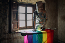 Unrecognizable Person In Silver Costume And Box On Head Ironing LGBTQ Flag While Standing In Shabby Abandoned Room