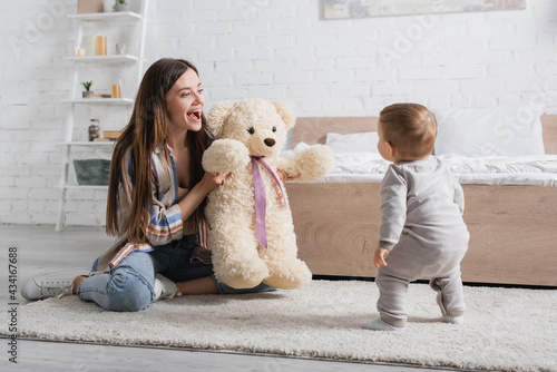 amazed young mother holding teddy bear near infant son