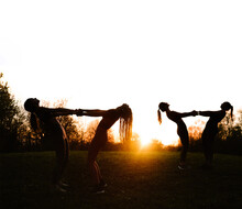 Side View Of Silhouettes Of Females Practicing Acro Yoga Together In Standing Backbend Pose While Holding Hands At Sundown In Park
