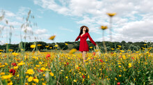 Happy Female In Red Sundress, Hat And Handbag Standing Looking Up On Blossoming Field With Yellow And Red Flowers With Outstretched Arms Enjoying On Warm Spring Summer Day