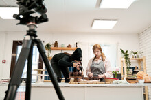 Unrecognizable Woman Taking Photo Of Chocolate Muffins On Digital Camera Against Blogger Talking During Cooking Process In Kitchen