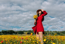 From Below Of Elegant Female In Hat Among Blooming Flowers In Countryside Field On Summer Day