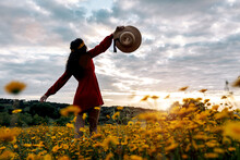 Back View Of Unrecognizable Female With Hat Enjoying Sundown In Countryside Field With Blossoming Flowers Under Cloudy Sky