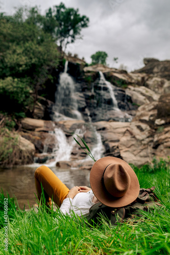 Anonymous male traveler in hat relaxing on lush lakeside and enjoying rapid cascade view in summer nature Wall mural