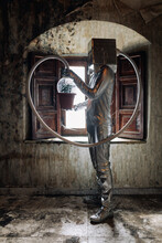 Side View Unrecognizable Person Wearing Silver Costume With Breathing Apparatus And Hose Attached To Potted Plant Standing In Shabby Abandoned Room