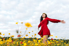 From Below Side View Of Trendy Female In Red Sundress And With Flower Crown Standing With Eyes Closed On Blossoming Field With Yellow And Red Flowers With Outstretched Arms On Warm Summer Day