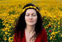 From Above Delighted Female In Red Sundress And With Flower Crown Standing With Eyes Closed On Blossoming Field With Yellow And Red Flowers Enjoying Warm Summer Day