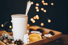 White Cup And Christmas Wooden Decorations, Cinnamon, Dried Oranges, Pine Cones In Box On Table On Black Background With Christmas Lights. Winter Holiday Time