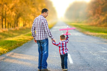 A Happy Parent Walks Along The Road With A Child And An Airplane In The Park On Nature Travel