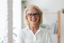 Headshot Portrait Of Smiling Senior Caucasian Businesswoman In Glasses Pose In Office On Working Day. Close Up Profile Picture Of Happy Middle-aged Female Employee Or CEO Show Success At Workplace.